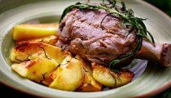 Stinco di maiale con patate al forno image