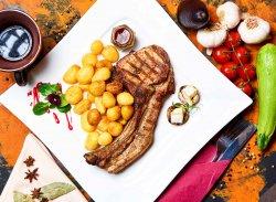 """Cotlet de porc Magnum """"La Conac"""" cu cartofi înabușiți în usturoi image"""