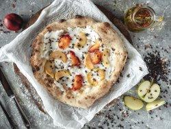 Pizza dolce con crema di mascarpone, fette di mela e pesca caramellate con scaglie di cioccolato image
