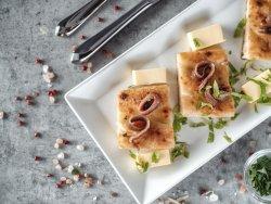 Fette di focaccia con filetti di acciughe marinate in casa con aglio,olio e prezzemolo, sul lettino di burro image