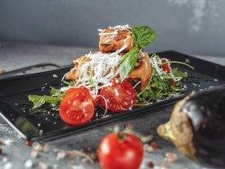 Melanzana con formaggio di pecora e miele su un lettino di rucola e pomodorini al forno image